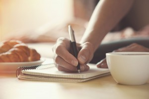 46651062 - female hands with pen writing on notebook with morning coffee and croissant